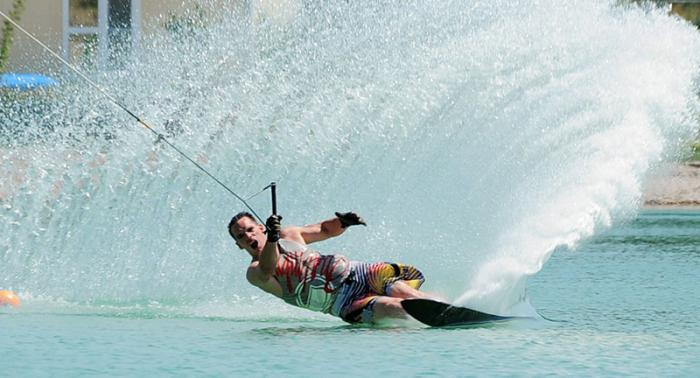 A cable skiing system makes it possible to learn and practice water skiing and wakeboarding at a constant speed.